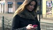 Pretty woman texting on smartphone in the city
