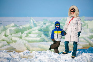 Young mother and her son on icy beach