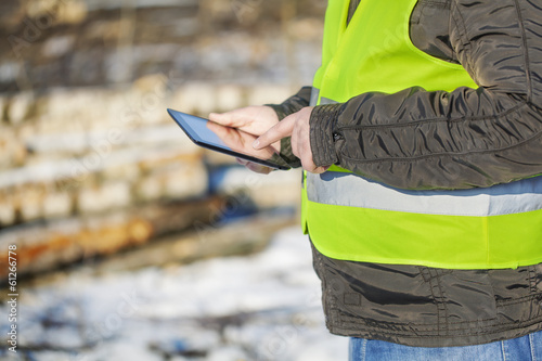 Lumberjack with tablet PC in cleared forest