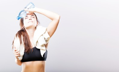 Exhausted woman with water bottle and towel