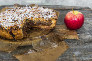 Apple pie and apple on old, rustic, wooden table