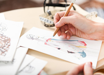 Dressmaker is drawing a fashion sketch