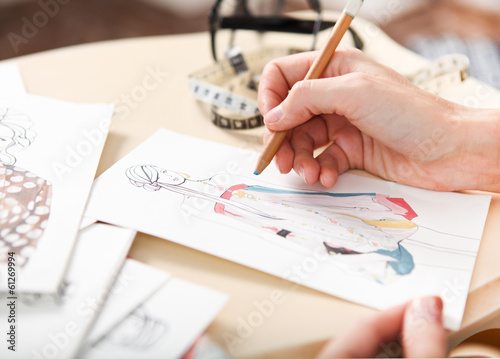 Dressmaker is drawing a fashion sketch