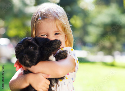 Cute little girl hugging dog puppy