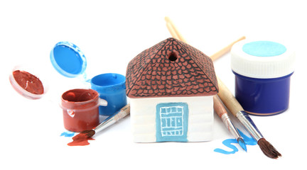 Hand made ceramic house and color paints isolated on white