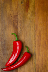 red hot chili peppers on a wooden background, vertical