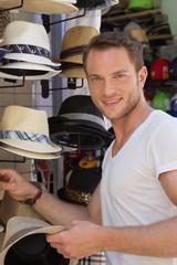 Gut aussehender junger Mann im Urlaub kauft einen Hut