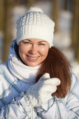 Woman portrait in winter clothes in sunlight