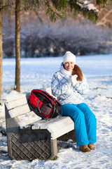 Pretty woman with backpack resting on a bench in winter park