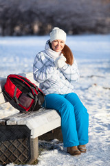 Young woman with backpack resting in winter park
