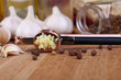 Composition with garlic press, fresh garlic and glass jars with