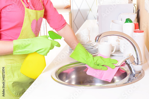 Beautiful young woman cleans in kitchen