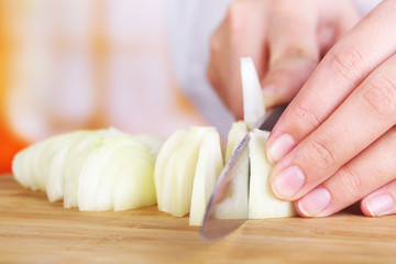 Female hands cutting bulb onion, on kitchen background