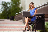attractive woman with laptop sitting on a bench in the city