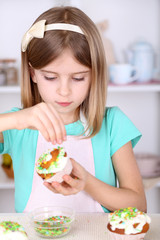 Little girl decorating cupcakes in kitchen at home