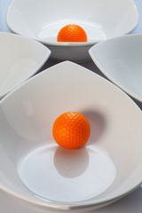 White ceramics bowls and orange golf ball
