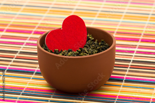 Red heart among tea leaves