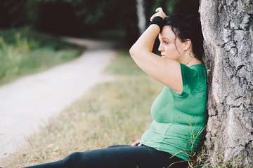 Exhausted overweight woman sitting down after training