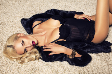 woman in black lingerie and fur coat lying on carpet