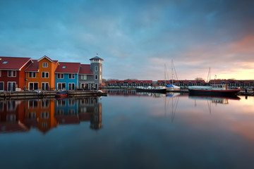 sunrise over marina with buildings and boats
