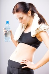 Woman looking at her flat stomach with water bottle