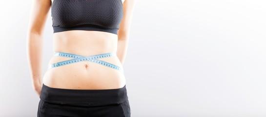 Woman measuring her waist, weight loss concept