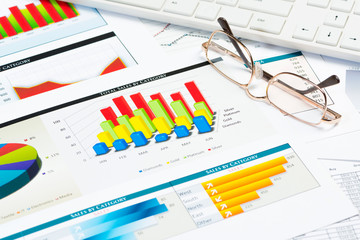 glasses, business papers with charts