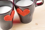cups of milk with decorative hearts on wood table