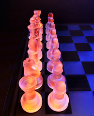 Glass chess on a chessboard lit by blue and orange light
