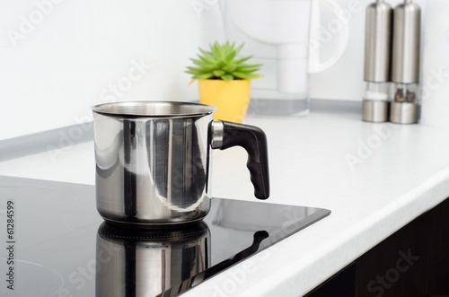 Mug in modern kitchen with induction stove - 61284599