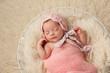 Newborn Baby Girl in Basket Wearing a Pink Bonnet