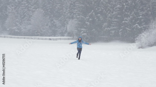 Young woman running across a snowy field