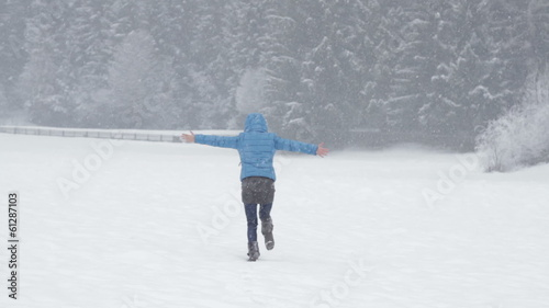 Rear view of young women running across a snowy field