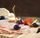 Sliced mortadella on wooden cooking board with bread, tomato and