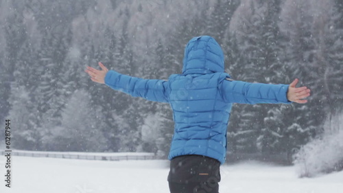 Woman with arms outstretched feeling the snow, slow motion