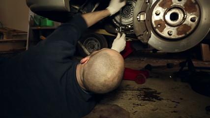 Car mechanic underneath a car fixing a clutch - Ver 3