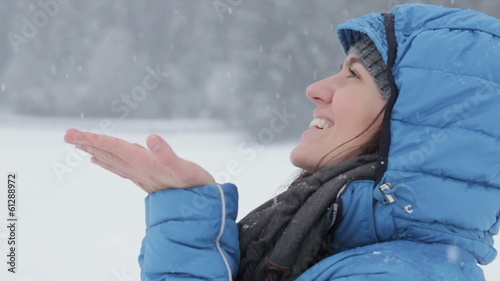 The young girl catches snowflakes, slow motion