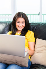 Asian woman using laptop on couch