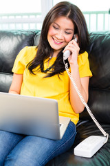 Asian woman using laptop and phone on couch
