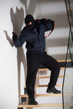 Armed robber on stairs