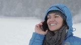 Woman talking on cellphone in winter scenery, outdoors