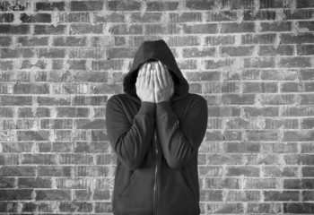 young man covers his face with hands with bricks wall