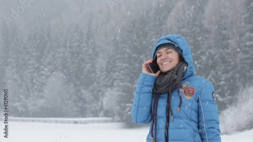 Woman talking on cellphone in winter scenery, slow motion