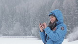 Woman texting with her phone in winter scenery, slow motion
