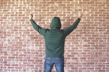 Happy and successful man cheering with his arms against wall