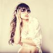 Fashion portrait of a beautiful young woman wearing sunglasses