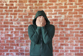 Young man covers his face with hands ,bricks wall as background