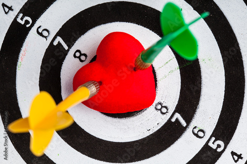 Target with two darts in heart love symbol as bullseye