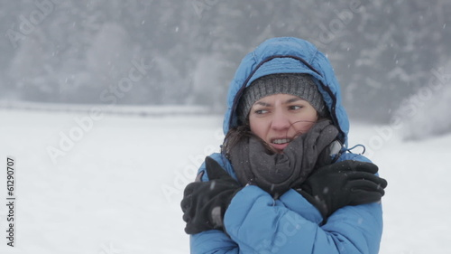 Young woman in winter clothes trying to warm up