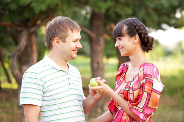Happy middle aged couple with apple.